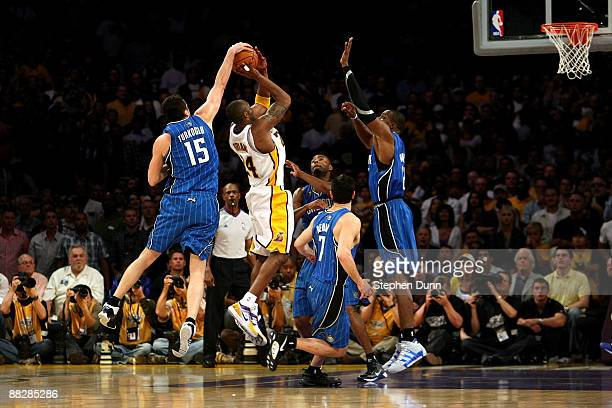 Kobe Bryant of the Los Angeles Lakers goes up for a shot over Hedo Turkoglu Rashard Lewis JJ Redick and Dwight Howard of the Orlando Magic in the...