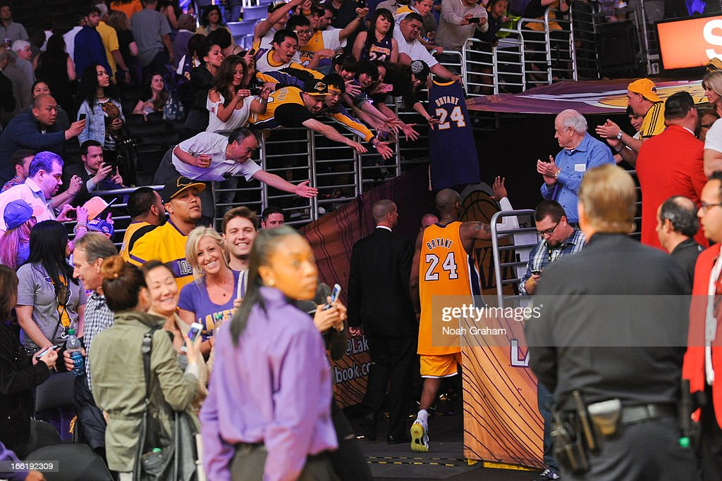 Kobe Bryant #24 of the Los Angeles Lakers greets fans after his team's victory against the New Orleans Hornets at Staples Center on April 9, 2013 in Los Angeles, California.