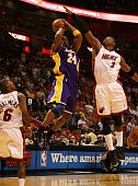 Kobe Bryant of the Los Angeles Lakers has his shot altered by the defense of Dwyane Wade and Mario Chalmers of the Miami Heat at American Airlines...