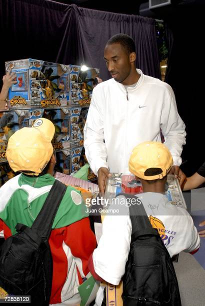 Kobe Bryant of the Los Angeles Lakers helps pass out gifts to the children during the Lakers Holiday Party on December 16 2006 at Toyota Training...