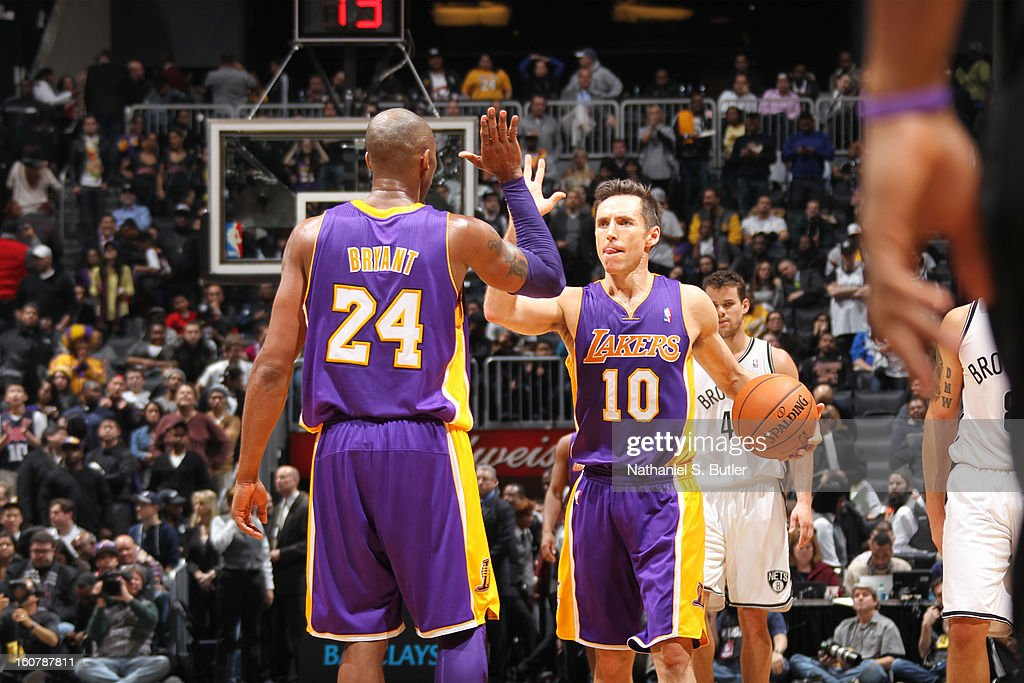 Kobe Bryant #24 of the Los Angeles Lakers high-fives teammate Steve Nash #10 during the game against the Brooklyn Nets on February 5, 2013 at the Barclays Center in the Brooklyn borough of New York City.
