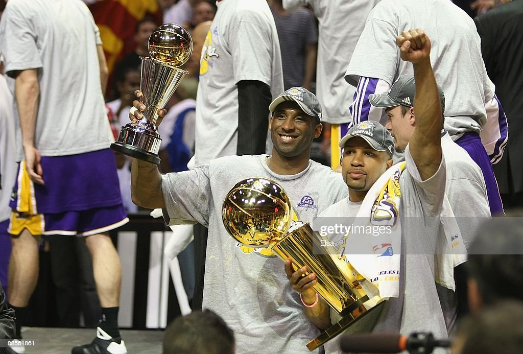 Kobe Bryant #24 of the Los Angeles Lakers holds the Bill Russell MVP trophy and Derek Fisher #2 of the Lakers holds the Larry O'Brien trophy after defeating the Orlando Magic in Game Five of the 2009 NBA Finals on June 14, 2009 at Amway Arena in Orlando, Florida. The Lakers won 99-86.