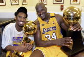 Kobe Bryant of the Los Angeles Lakers holds the Larry O'Brian trophy as teammate Shaquille O'Neal hold the MVP trophy after winning the NBA...