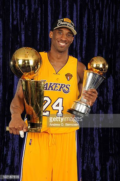 Kobe Bryant of the Los Angeles Lakers holds the Larry O'Brien Trophy and the Bill Russell MVP Trophy following his team's victory over the Boston...