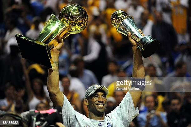 Kobe Bryant of the Los Angeles Lakers holds up the Larry O'Brien trophy and the MVP trophy after the Lakers defeated the Orlando Magic 9986 in Game...