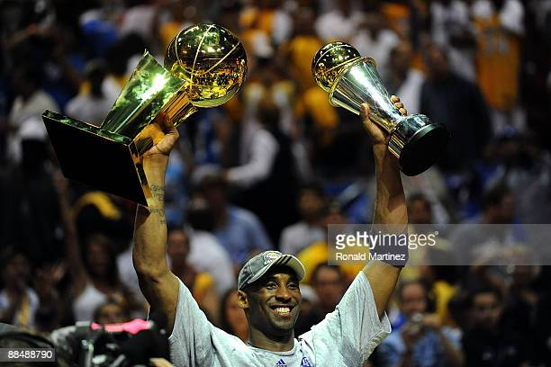 Kobe Bryant of the Los Angeles Lakers holds up the Larry O'Brien trophy and the Bill Russell MVP trophy after the Lakers defeated the Orlando Magic...