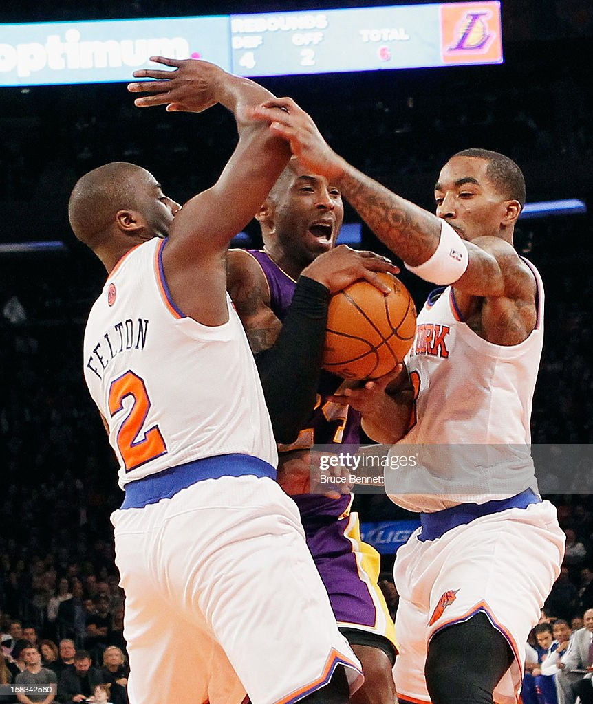 Kobe Bryant #24 of the Los Angeles Lakers is stopped by Raymond Felton #2 and J.R. Smith #8 of the New York Knicks in the first quarter at Madison Square Garden on December 13, 2012 in New York City.