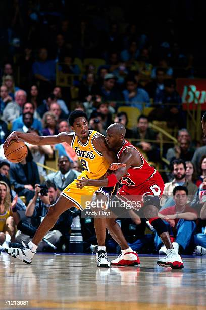 Kobe Bryant of the Los angeles Lakers keeps the ball away from Michael Jordan of the Chicago Bulls as he back in closer to the basket during an NBA...