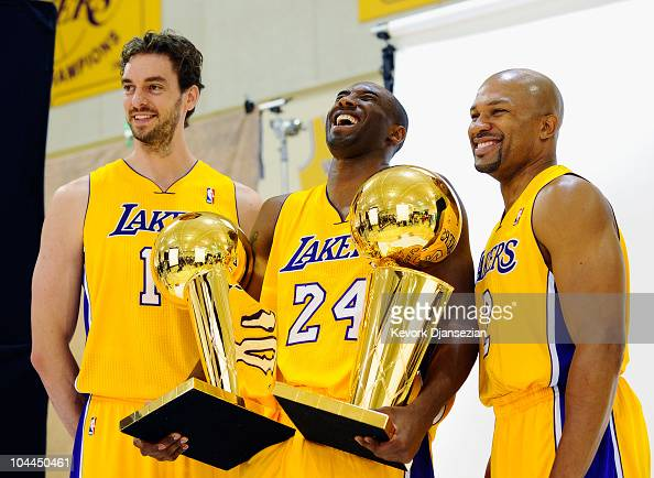 Kobe Bryant of the Los Angeles Lakers laughs as he holds two NBA Finals Larry O'Brien Championship Trophy's as he poses for a photograph with...