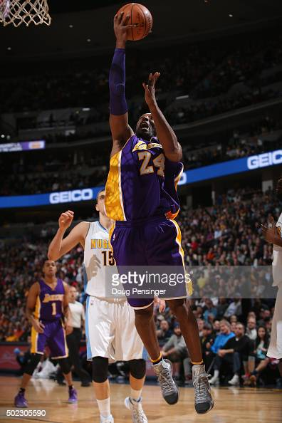 Kobe Bryant of the Los Angeles Lakers lays up a shot against Nikola Jokic of the Denver Nuggets at Pepsi Center on December 22 2015 in Denver...