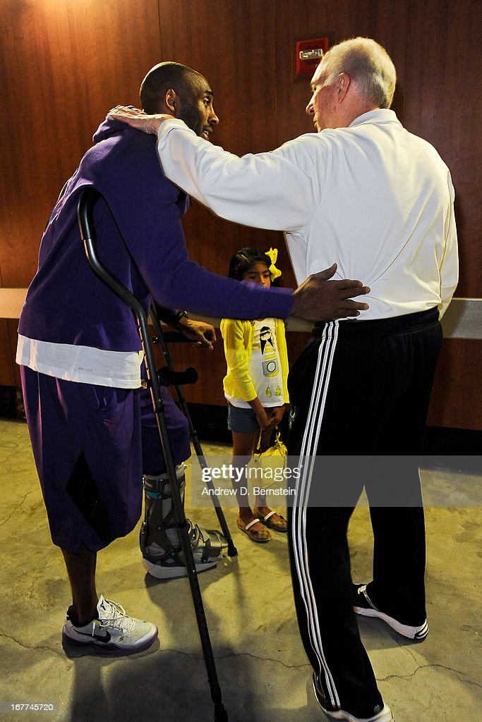 Kobe Bryant #24 of the Los Angeles Lakers, on crutches due to an injury, greets Gregg Popovich, head coach of the San Antonio Spurs, before Game Four of the Western Conference Quarterfinals during the 2013 NBA Playoffs at Staples Center on April 28, 2013 in Los Angeles, California.