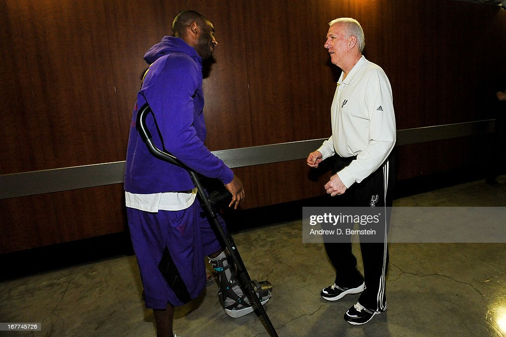 Kobe Bryant #24 of the Los Angeles Lakers, on crutches due to an injury, speaks with Gregg Popovich, head coach of the San Antonio Spurs, before Game Four of the Western Conference Quarterfinals during the 2013 NBA Playoffs at Staples Center on April 28, 2013 in Los Angeles, California.