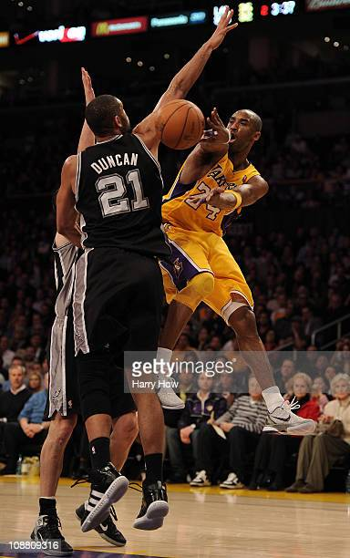 Kobe Bryant of the Los Angeles Lakers passes around Tim Duncan of the San Antonio Spurs during the first half at Staples Center on February 3 2011 in...