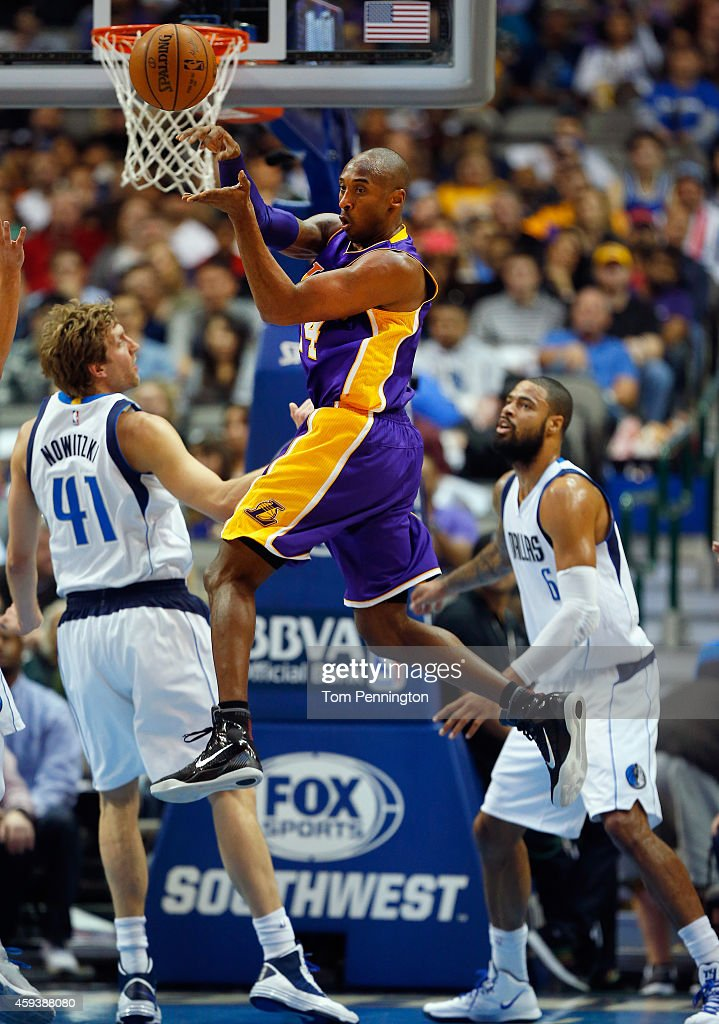 Kobe Bryant of the Los Angeles Lakers passes the ball against Dirk Nowitzki of the Dallas Mavericks and Tyson Chandler of the Dallas Mavericks in the...