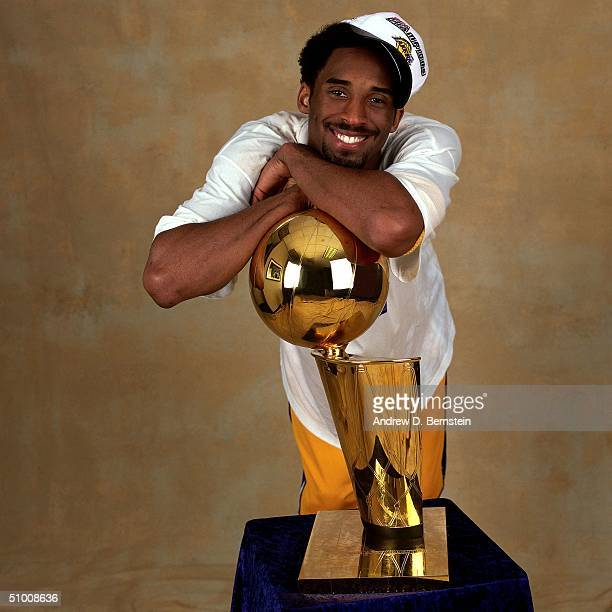 Kobe Bryant of the Los Angeles Lakers poses for a portrait with the championship trophy circa 2000 in Los Angeles California NOTE TO USER User...
