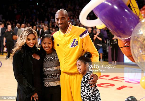 Kobe Bryant of the Los Angeles Lakers poses with wife Vanessa and daughters Giana and Natalia during a ceremony honoring Bryant for moving into third...