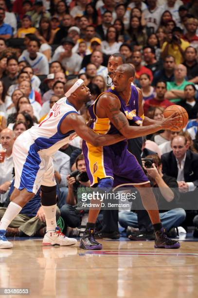 Kobe Bryant of the Los Angeles Lakers posts up against Baron Davis of the Los Angeles Clippers in the home opener at Staples Center on October 29...