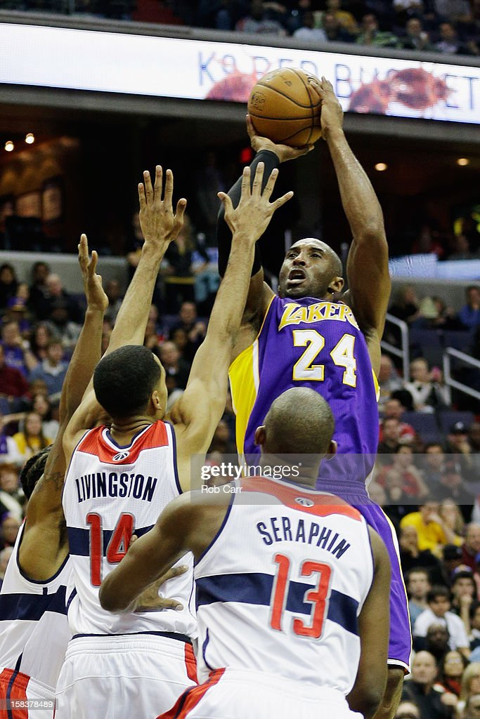 Kobe Bryant #24 of the Los Angeles Lakers puts up a shot in front of Shaun Livingston #14 and Kevin Seraphin #13 of the Washington Wizards during the first half at Verizon Center on December 14, 2012 in Washington, DC.