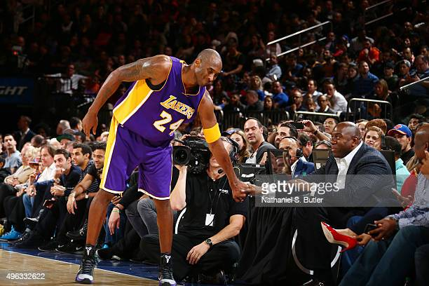 Kobe Bryant of the Los Angeles Lakers reaches out to Magic Johnson during the game against the New York Knicks on November 8 2015 at Madison Square...