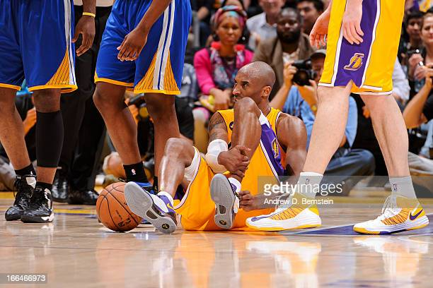 Kobe Bryant of the Los Angeles Lakers reacts on the floor after getting injured during a game against the Golden State Warriors at Staples Center on...