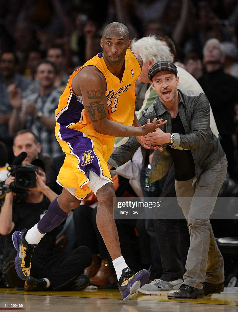 Kobe Bryant of the Los Angeles Lakers reacts with Justin Timberlake after Bryant makes a basket in the fourth quarter against the Denver Nuggets in...