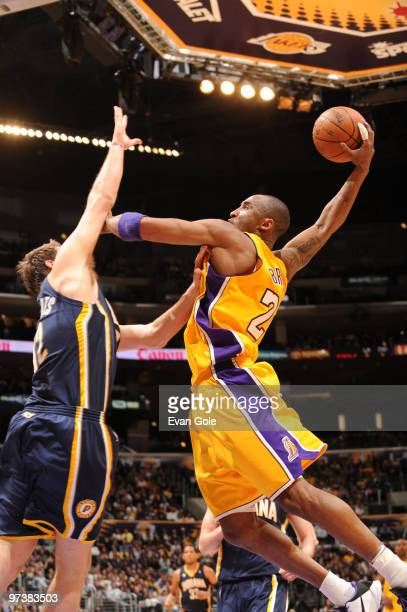 Kobe Bryant of the Los Angeles Lakers rises for a dunk against Josh McRoberts of the Indiana Pacers at Staples Center on March 2 2010 in Los Angeles...
