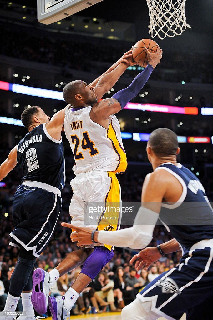 Kobe Bryant #24 of the Los Angeles Lakers rises for a reverse dunk against Thabo Sefolosha #2 of the Oklahoma City Thunder at Staples Center on January 27, 2013 in Los Angeles, California.