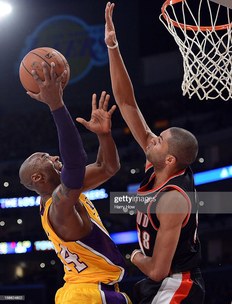 Kobe Bryant #24 of the Los Angeles Lakers scores on a layup in front of Nicolas Batum #88 of the Portland Trail Blazers at Staples Center on December 28, 2012 in Los Angeles, California.