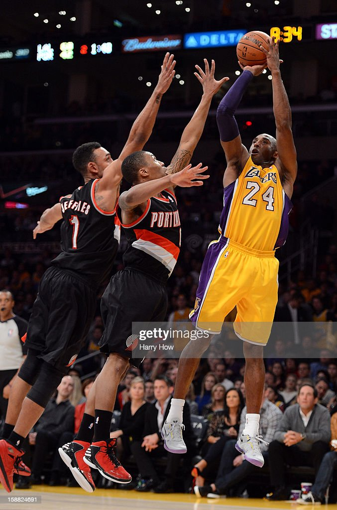 Kobe Bryant #24 of the Los Angeles Lakers shoots a jumper in front of Jared Jeffries #1 and Luke Babbitt #8 of the Portland Trail Blazers at Staples Center on December 28, 2012 in Los Angeles, California. The Lakers won 104-87.