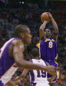 Kobe Bryant of the Los Angeles Lakers shoots a jumper over Raja Bell and James Jones of the Phoenix Suns in the third quarter of game seven of the...