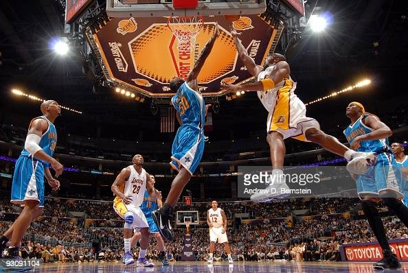 Kobe Bryant of the Los Angeles Lakers shoots a layup against Emeka Okafor of the New Orleans Hornets during the game at Staples Center on November 8...