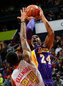 Kobe Bryant of the Los Angeles Lakers shoots against Kent Bazemore of the Atlanta Hawks at Philips Arena on December 4 2015 in Atlanta Georgia NOTE...