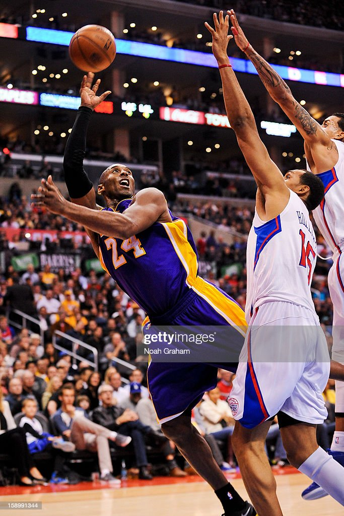 Kobe Bryant #24 of the Los Angeles Lakers shoots against Ryan Hollins #15 and Matt Barnes #22 of the Los Angeles Clippers at Staples Center on January 4, 2013 in Los Angeles, California.