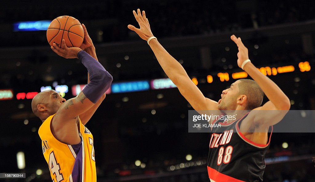 Kobe Bryant (L) of the Los Angeles Lakers shoots before Nicolas Batum (R) of the Portland Trail Blazers during their NBA game on December 28, 2012 at Staples Center in Los Angeles, California. AFP PHOTO / Joe KLAMAR