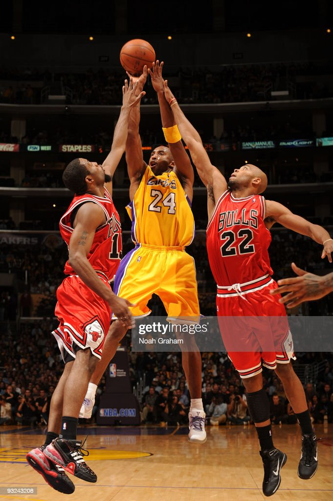 Kobe Bryant of the Los Angeles Lakers shoots between John Salmons and Taj Gibson of the Chicago Bulls at Staples Center on November 19 2009 in Los...
