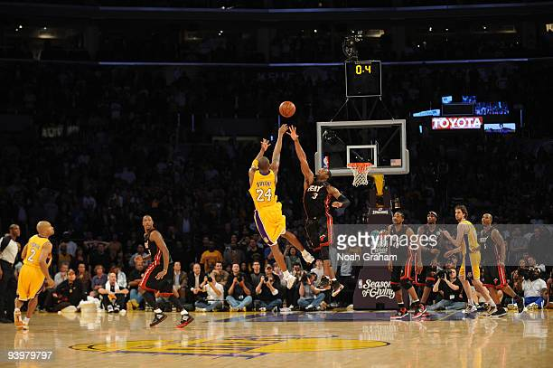 Kobe Bryant of the Los Angeles Lakers shoots over Dwyane Wade of the Miami Heat with 04 seconds remaining for the win at Staples Center on December 4...