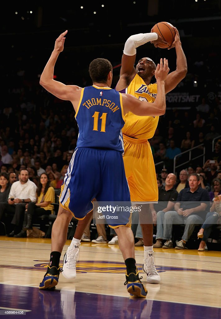 Kobe Bryant #24 of the Los Angeles Lakers shoots while defended by Klay Thompson #11 of the Golden State Warriors in the first half at Staples Center on October 9, 2014 in Los Angeles, California.