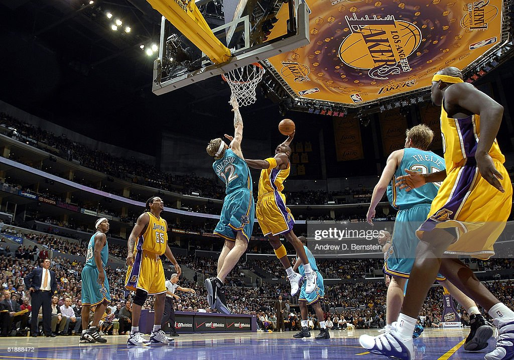 Kobe Bryant #8 of the Los Angeles Lakers slam dunks over Chris Andersen #12 of the New Orleans Hornets on December 22, 2004 at the Staples Center in Los Angeles, California.