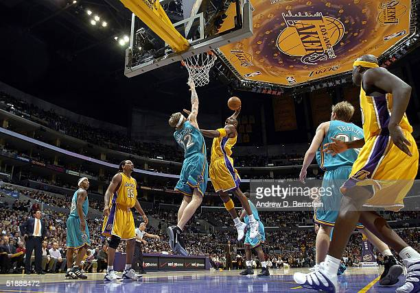 Kobe Bryant of the Los Angeles Lakers slam dunks over Chris Andersen of the New Orleans Hornets on December 22 2004 at the Staples Center in Los...