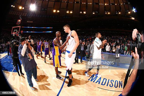 Kobe Bryant of the Los Angeles Lakers speaks with Kristaps Porzingis of the New York Knicks after the game on November 8 2015 at Madison Square...
