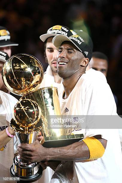 Kobe Bryant of the Los Angeles Lakers struggles to hold both the Larry O'Brien trophy and the MVP trophy after the Lakers defeated the Boston Celtics...