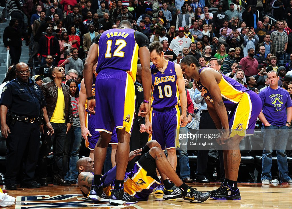 Kobe Bryant of the Los Angeles Lakers surrounded by teammates goes down with an ankle injury during the game against the Atlanta Hawks on March 13, 2013 at Philips Arena in Atlanta, Georgia.