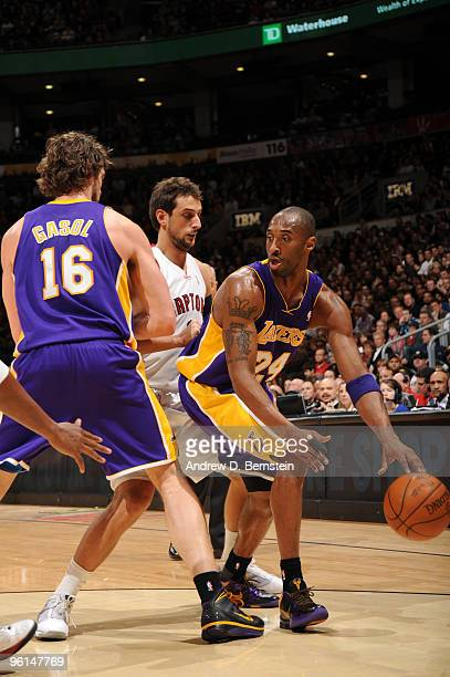 Kobe Bryant of the Los Angeles Lakers takes advantage of the pick set by teammate Pau Gasol on Marco Belinelli of the Toronto Raptors during a game...