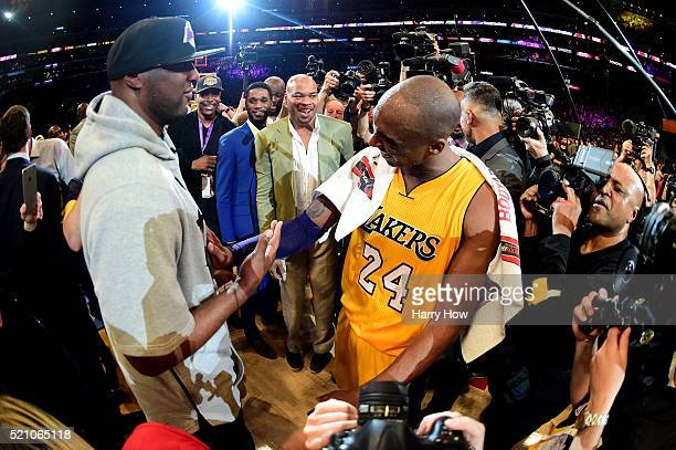 Kobe Bryant of the Los Angeles Lakers talks with former teammate Lamar Odom after scoring 60 points in his final NBA game at Staples Center on April...