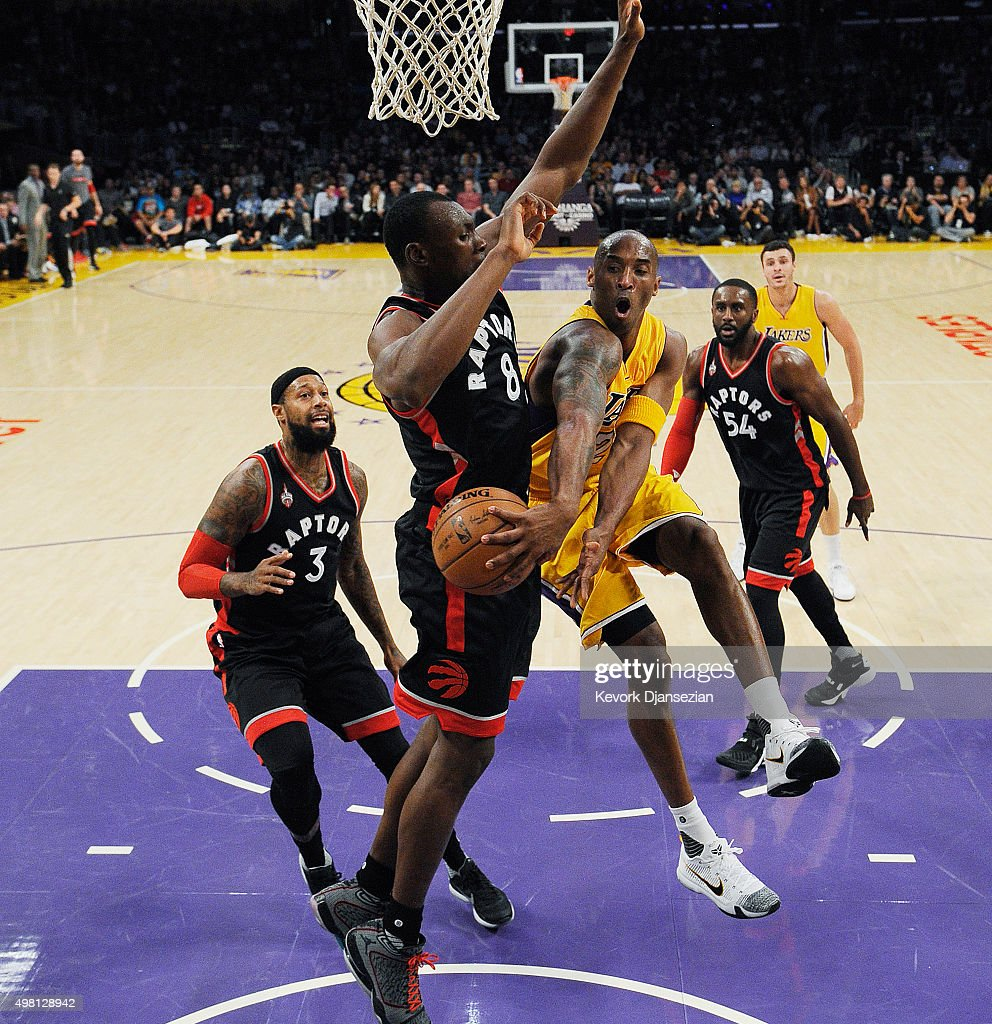 Kobe Bryant of the Los Angeles Lakers throws a wrap around pass against Bismack Biyombo of the Toronto Raptors during the first half of the...