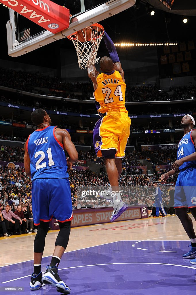 Kobe Bryant #24 of the Los Angeles Lakers throws down a reverse dunk while Thaddeus Young #21 of the Philadelphia 76ers looks on at Staples Center on January 1, 2013 in Los Angeles, California.