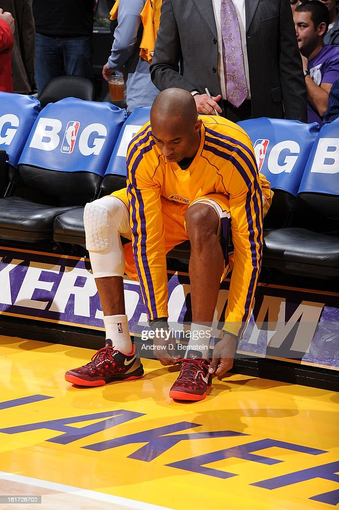 Kobe Bryant #24 of the Los Angeles Lakers ties his shoe at halftime of a game against the Los Angeles Clippers at Staples Center on February 14, 2013 in Los Angeles, California.