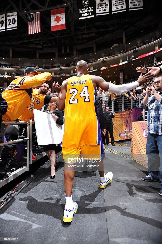 Kobe Bryant #24 of the Los Angeles Lakers walks away giving high fives to fans against the New Orleans Hornets at Staples Center on April 9, 2013 in Los Angeles, California.