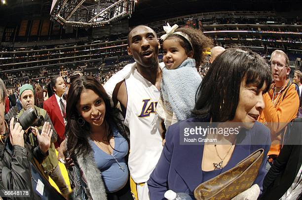 Kobe Bryant of the Los Angeles Lakers walks off the court with his wife Vanessa and daughter Natalia after he scored 81 points against the Toronto...