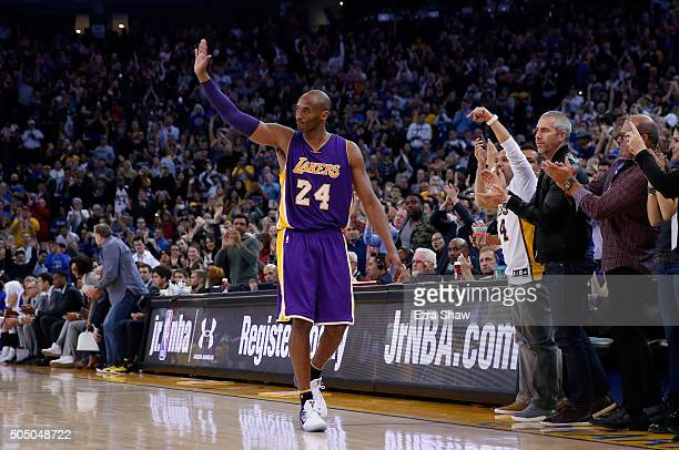 Kobe Bryant of the Los Angeles Lakers waves to the crowd after being taken out of the game in the fourth quarter against the Golden State Warriors at...